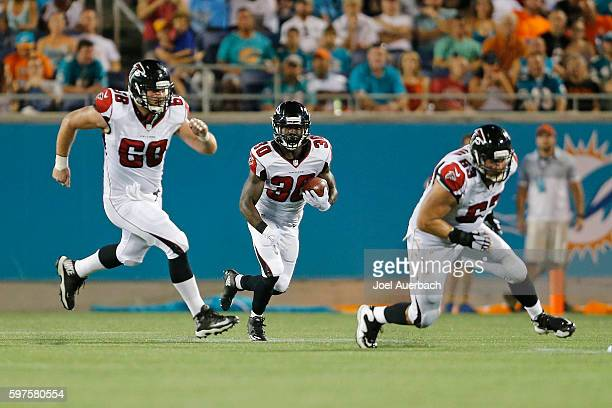 Jacob Tamme and Mike Person lead Cyrus Gray of the Atlanta Falcons as he runs with the ball against the Miami Dolphins during a preseason game on...