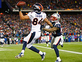 Jacob Tamme of the Denver Broncos drops a pass as Patrick Chung of the New England Patriots defends during the fourth quarter at Gillette Stadium on...