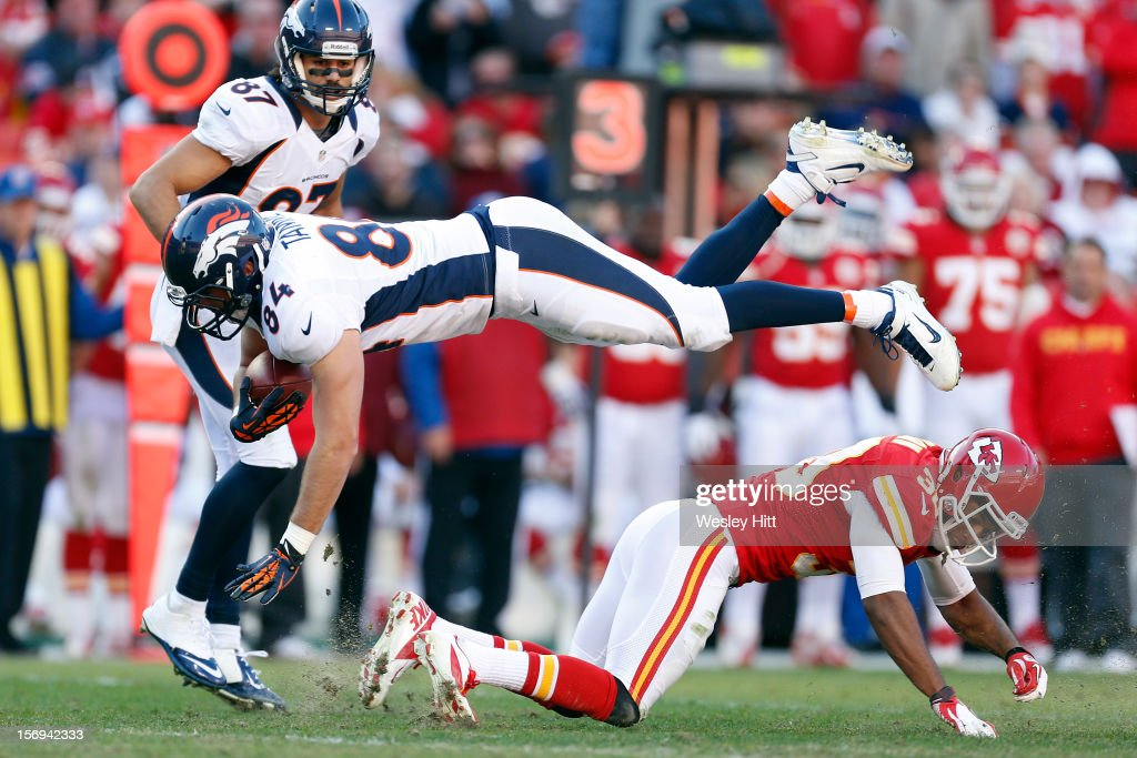 Jacob Tamme #84 of the Denver Broncos is tackled by Jalil Brown #30 of the Kansas City Chiefs at Arrowhead Stadium on November 25, 2012 in Kansas City, Missouri. The Broncos defeated the Chiefs 17-9.