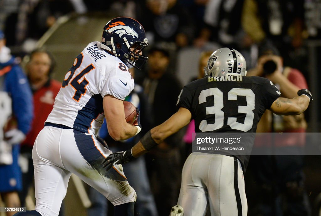 Jacob Tamme #84 of the Denver Broncos runs with the ball after a short reception pursued by Tyvon Branch #33 of the Oakland Raiders in the first quarter at Oakland-Alameda County Coliseum on December 6, 2012 in Oakland, California. The Broncos won the game 26-13.