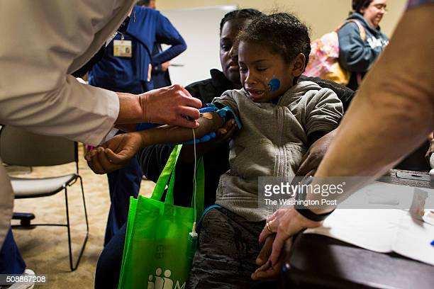 Jacob Thomas of Flint Mich is held by his mother Alexis Taylor as he gets his blood drawn in order to test his blood lead levels at Carriage Town...