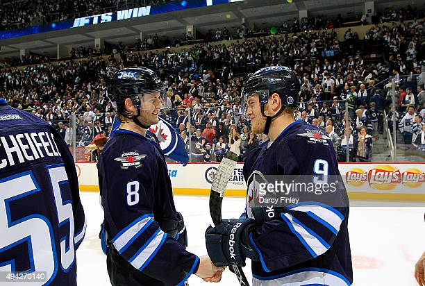 Jacob Trouba and Andrew Copp of the Winnipeg Jets shake hands as they celebrate a 54 victory over the Minnesota Wild at the MTS Centre on October 25...