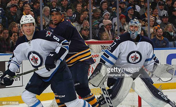 Jacob Trouba and Connor Hellebuyck of the Winnipeg Jets defend against Evander Kane of the Buffalo Sabres during an NHL game at the KeyBank Center on...