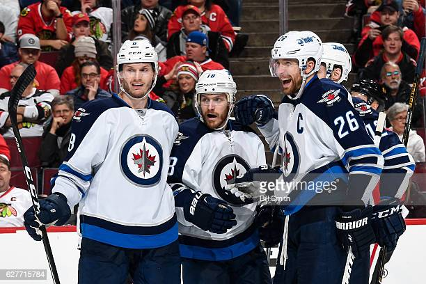 Jacob Trouba Bryan Little and Blake Wheeler of the Winnipeg Jets react after Little scored against the Chicago Blackhawks in the second period at the...