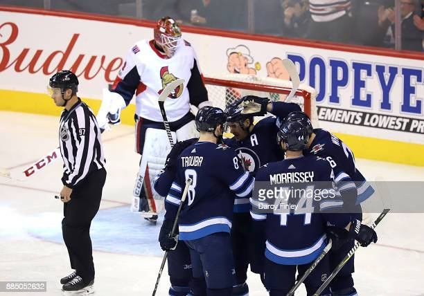 Jacob Trouba Mark Scheifele Josh Morrissey and Blake Wheeler of the Winnipeg Jets celebrate a second period goal against the Ottawa Senators at the...