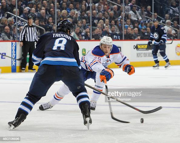 Jacob Trouba of the Winnipeg Jets and Leon Draisaitl of the Edmonton Oilers battle for the loose puck during third period action on December 3 2014...
