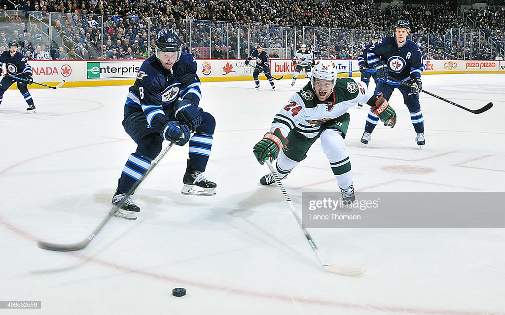 <a gi-track='captionPersonalityLinkClicked' href=/galleries/search?phrase=Jacob+Trouba&family=editorial&specificpeople=8050718 ng-click='$event.stopPropagation()'>Jacob Trouba</a> #8 of the Winnipeg Jets and <a gi-track='captionPersonalityLinkClicked' href=/galleries/search?phrase=Matt+Cooke&family=editorial&specificpeople=592551 ng-click='$event.stopPropagation()'>Matt Cooke</a> #24 of the Minnesota Wild reach for the loose puck during third period action at the MTS Centre on December 27, 2013 in Winnipeg, Manitoba, Canada.