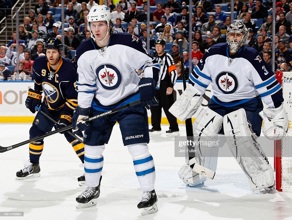 <a gi-track='captionPersonalityLinkClicked' href=/galleries/search?phrase=Jacob+Trouba&family=editorial&specificpeople=8050718 ng-click='$event.stopPropagation()'>Jacob Trouba</a> #8 of the Winnipeg Jets and <a gi-track='captionPersonalityLinkClicked' href=/galleries/search?phrase=Steve+Ott&family=editorial&specificpeople=210616 ng-click='$event.stopPropagation()'>Steve Ott</a> #9 of the Buffalo Sabres keep an eye on the puck as Ondrej Pavelec #31 of Winnipeg guards the net at First Niagara Center on December 17, 2013 in Buffalo, New York. Buffalo defeated Winnipeg 4-2.