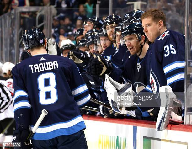 Jacob Trouba of the Winnipeg Jets celebrates his second period goal against the New Jersey Devils with teammates at the bench at the Bell MTS Place...