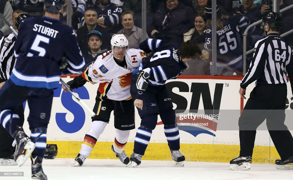 Jacob Trouba #8 of the Winnipeg Jets fights Sam Bennett #93 of the Calgary Flames during NHL action on March 11, 2017 at the MTS Centre in Winnipeg, Manitoba.