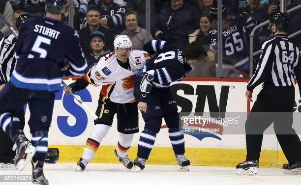 Jacob Trouba of the Winnipeg Jets fights Sam Bennett of the Calgary Flames during NHL action on March 11 2017 at the MTS Centre in Winnipeg Manitoba