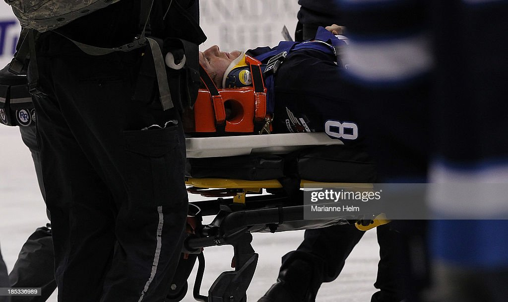 Jacob Trouba #8 of the Winnipeg Jets is taken off the ice on a stretcher after he crashed into the boards in second-period action of an NHL game against the St. Louis Blues at the MTS Centre on October 18, 2013 in Winnipeg, Manitoba, Canada.