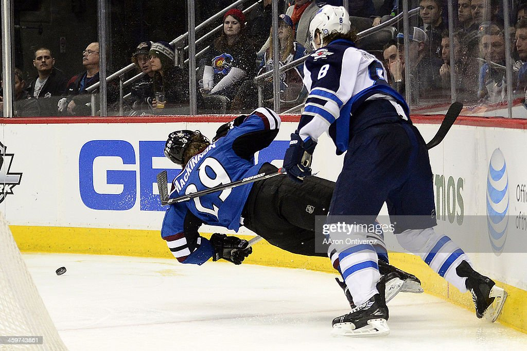 Jacob Trouba (8) of the Winnipeg Jets lays out Nathan MacKinnon (29) of the Colorado Avalanche during the third period of action. The Colorado Avalanche lost 2-1 to the Winnipeg Jets at the Pepsi Center on Sunday, December 29, 2013.