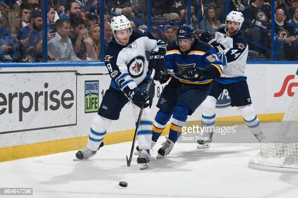 Jacob Trouba of the Winnipeg Jets makes a pass as David Perron of the St Louis Blues pressures on April 4 2017 at Scottrade Center in St Louis...