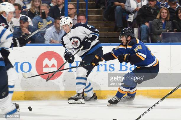 Jacob Trouba of the Winnipeg Jets makes a pass as Magnus Paajarvi of the St Louis Blues pressures on April 4 2017 at Scottrade Center in St Louis...