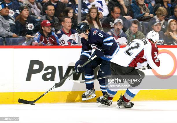 Jacob Trouba of the Winnipeg Jets plays the puck along the boards as Francois Beauchemin of the Colorado Avalanche defends during second period...