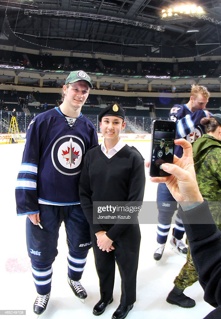 Jacob Trouba #8 of the Winnipeg Jets poses with a member of the Canadian Armed Forces following NHL action against the Ottawa Senators for Canadian Armed Forces Appreciation Night on March 4, 2015 at the MTS Centre in Winnipeg, Manitoba, Canada.