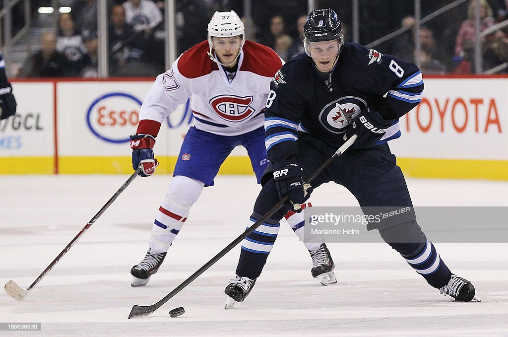 <a gi-track='captionPersonalityLinkClicked' href=/galleries/search?phrase=Jacob+Trouba&family=editorial&specificpeople=8050718 ng-click='$event.stopPropagation()'>Jacob Trouba</a> #8 of the Winnipeg Jets skates with the puck down the ice as he is followed by <a gi-track='captionPersonalityLinkClicked' href=/galleries/search?phrase=Alex+Galchenyuk&family=editorial&specificpeople=7419137 ng-click='$event.stopPropagation()'>Alex Galchenyuk</a> #27 of the Montreal Canadiens during second period action in an NHL game at the MTS Centre on October 15, 2013 in Winnipeg, Manitoba, Canada.