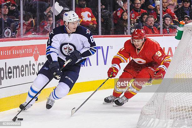 Jacob Trouba of the Winnipeg Jets skates with the puck past Jyrki Jokipakka of the Calgary Flames during an NHL game at Scotiabank Saddledome on...