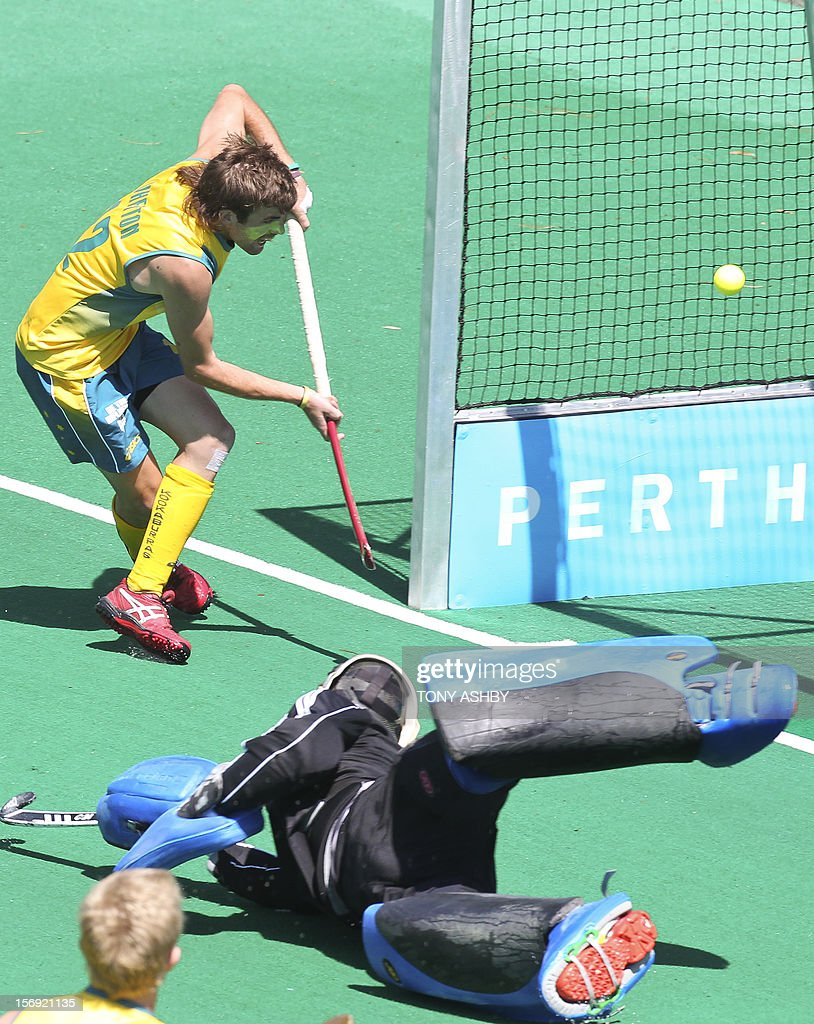 Jacob Whetton of Australia (top) beats England goalkeeper Patrick Smith (front) to score during their match on the final day of the International Super Series hockey tournament in Perth on November 25, 2012. AFP PHOTO / Tony ASHBY IMAGE STRICTLY FOR EDITORIAL USE - STRICTLY NO COMMERCIAL USE