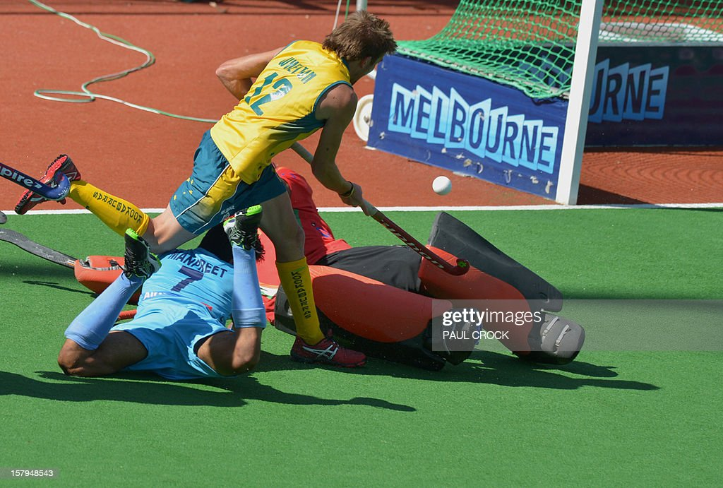 Jacob Whetton of Australia (top-in yellow) fights his way through defenders Manpreet Singh (bottom L) and goalkeeper PT Roa (R-in red) of India during the second semi-final at the men's Hockey Champions Trophy tournament in Melbourne on December 8, 2012. IMAGE STRICTLY RESTRICTED TO EDITORIAL USE - STRICTLY NO COMMERCIAL USE AFP PHOTO/Paul CROCK