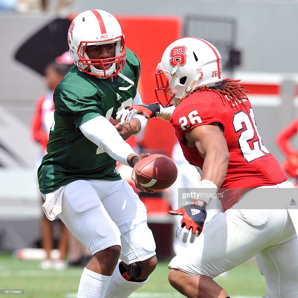 Jacoby Brissett #12 hands off to Tony Creecy #26 of the North Carolina State Wolfpack during the Kay Yow Spring Football Game at Carter-Finley Stadium on April 20, 2013 in Raleigh, North Carolina.