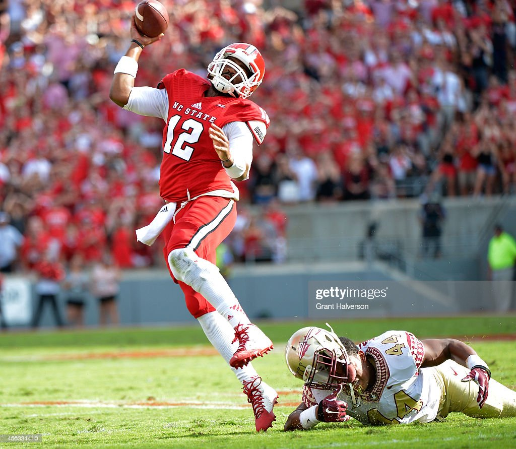 Jacoby Brissett #12 of the North Carolina State Wolfpack breaks free from DeMarcus Walker #44 of the Florida State Seminoles to throw a touchdown pass during the first quarter of their game at Carter-Finley Stadium on September 27, 2014 in Raleigh, North Carolina.