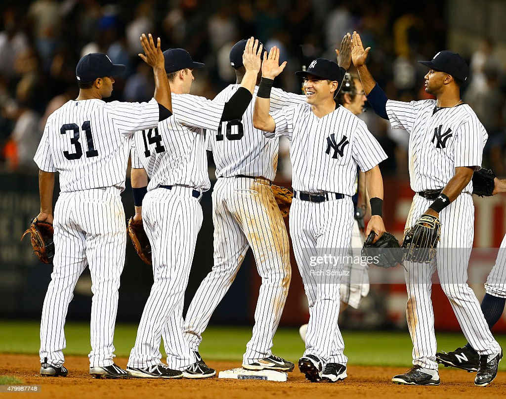 Jacoby Ellsbury and Chris Young #24 are congratulated by teammates after defeating the Oakland Athletics 5-4 during a MLB baseball game at Yankee Stadium on July 8, 2015 in the Bronx borough of New York City. The Yankees defeated the A's 5-4.