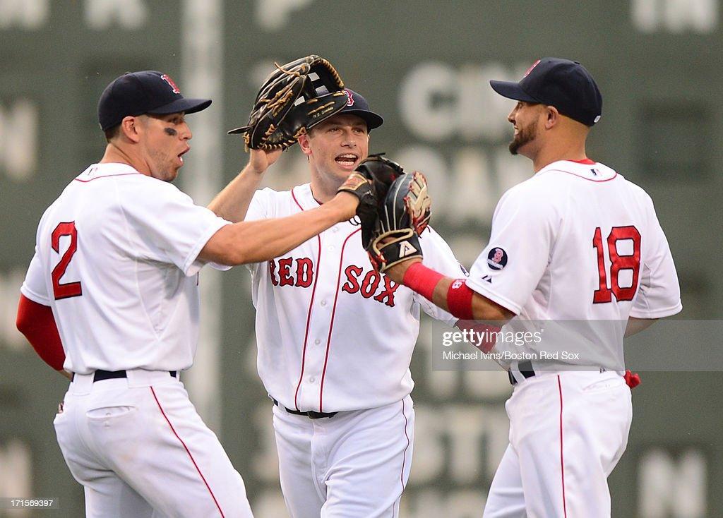 Jacoby Ellsbury #2, Daniel Nava #29 and Shane Victorino #18 of the Boston Red Sox celebrate a 5-3 win against the Colorado Rockies on June 26, 2013 at Fenway Park in Boston, Massachusetts.