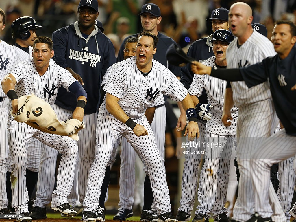 Jacoby Ellsbury #22, Mark Teixeira #25, Brian McCann #34 and the rest of the of the New York Yankees wait for Chase Headley #12 after his walk off home run in the ninth inning to defeat of the Boston Red Sox 5-4 during a MLB baseball game at Yankee Stadium on September 4, 2014 in the Bronx borough of New York City.