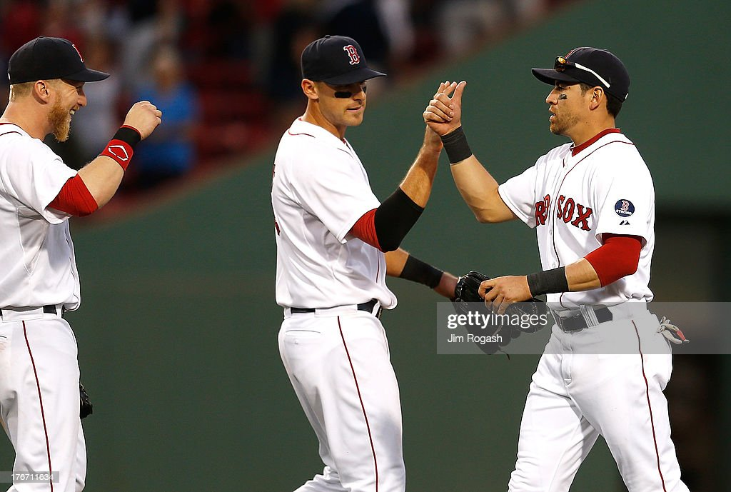 Jacoby Ellsbury #2 of the Boston Red Sox celebrates a 6-1 win over the New York Yankees with teammates Mike Carp #37 and Will Middlebrooks #16 at Fenway Park on August 17, 2013 in Boston, Massachusetts.