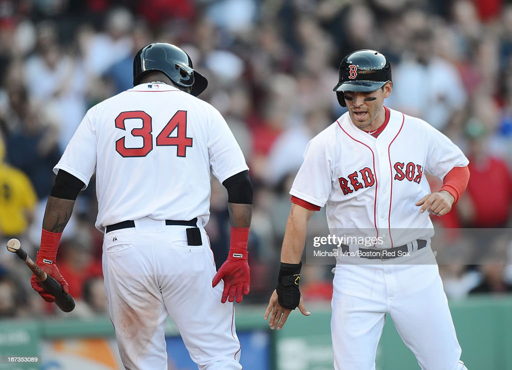 Jacoby Ellsbury #2 of the Boston Red Sox is congratulated by David Ortiz #34 after scoring against the Oakland Athletics in the fifth inning on April 24, 2013 at Fenway Park in Boston, Massachusetts.