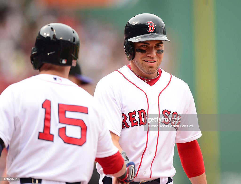 Jacoby Ellsbury #2 of the Boston Red Sox is congratulated by Dustin Pedroia #15 after scoring a run against the Colorado Rockies in the first inning on June 26, 2013 at Fenway Park in Boston, Massachusetts.