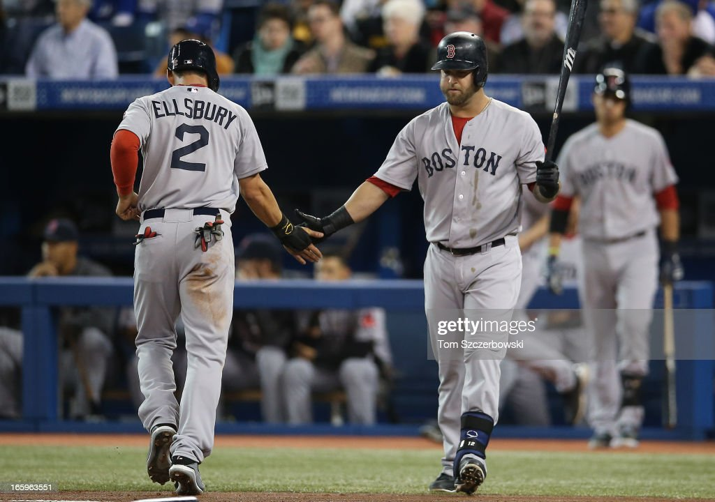 Jacoby Ellsbury #2 of the Boston Red Sox is congratulated by Mike Napoli #12 after scoring a run on an RBI single by Dustin Pedroia #15 in the first inning during MLB game action against the Toronto Blue Jays on April 7, 2013 at Rogers Centre in Toronto, Ontario, Canada.