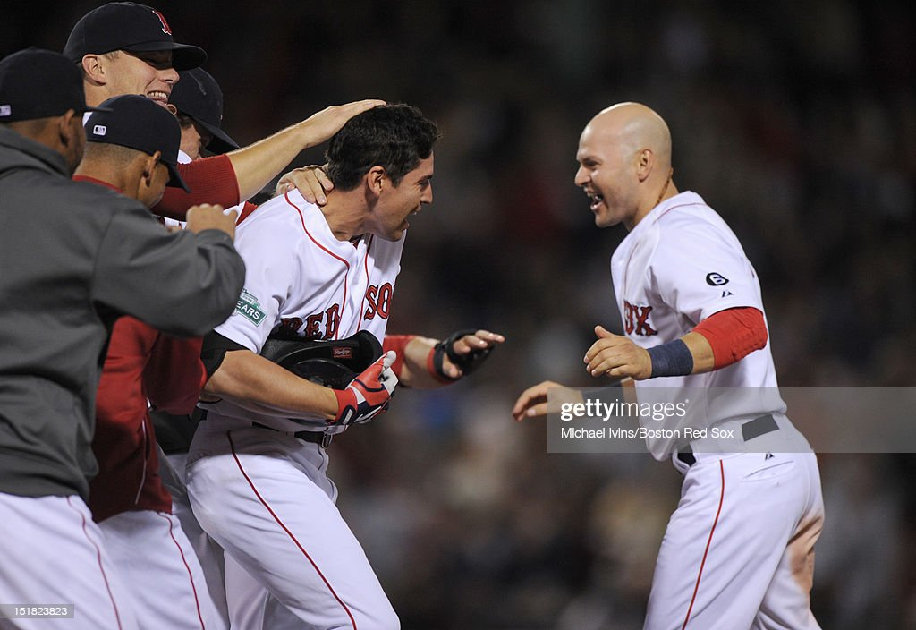 Jacoby Ellsbury #2 of the Boston Red Sox is mobbed by teammates including Cody Ross #7, right, after hitting a game-winning single against the New York Yankees in the ninth inning on September 11, 2012 at Fenway Park in Boston, Massachusetts.