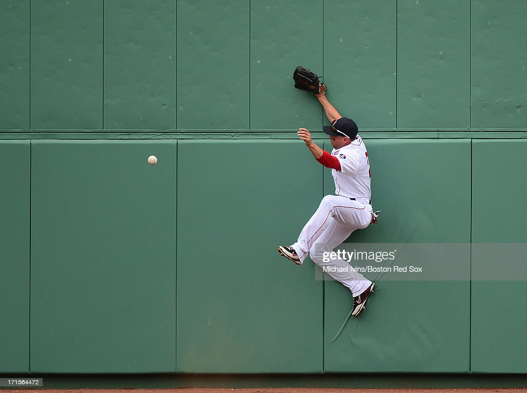 Jacoby Ellsbury #2 of the Boston Red Sox leaps but can not catch a fly ball against the Colorado Rockies in the fourth inning on June 26, 2013 at Fenway Park in Boston, Massachusetts.