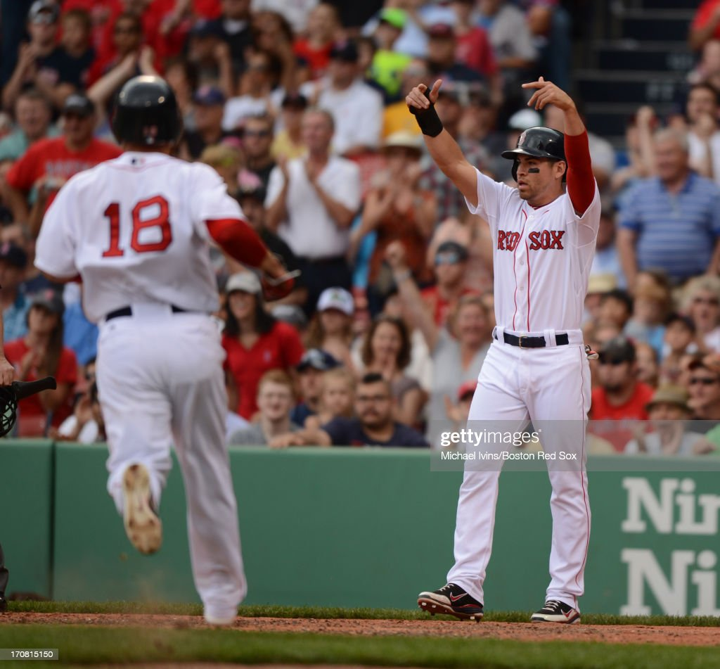 Jacoby Ellsbury #2 of the Boston Red Sox signals to Shane Victorino #18 to remain on his feet after scoring a run against the Tampa Bay Rays in the third inning on June 18, 2013 at Fenway Park in Boston, Massachusetts.
