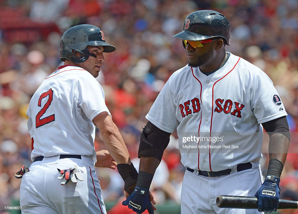 Jacoby Ellsbury #2 of the Boston Red Sox slaps hands with David Ortiz #34 after scoring a run against the Tampa Bay Rays in the first inning on June 18, 2013 at Fenway Park in Boston, Massachusetts.