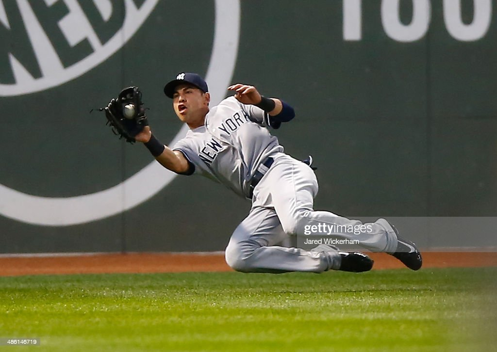 Jacoby Ellsbury of the New York Yankees catches a fly ball in center field against the Boston Red Sox in the first inning during the game at Fenway...