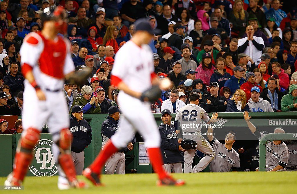 Jacoby Ellsbury #22 of the New York Yankees is congratulated after scoring in the fifth inning against the Boston Red Sox during the game at Fenway Park on April 22, 2014 in Boston, Massachusetts.