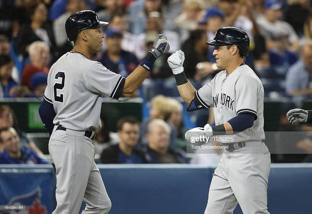 Jacoby Ellsbury of the New York Yankees is congratulated by Derek Jeter after hitting a tworun home run in the seventh inning during MLB game action...