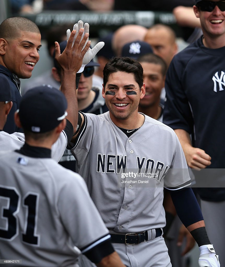 Jacoby Ellsbury #22 of the New York Yankees is greeted by teammates in the dugout after hitting a solo home run in the 10th inning against the Chicago White Sox as he crosses the plate at U.S. Cellular Field on May 24, 2014 in Chicago, Illinois. The Yankees defeated the White Sox 4-3 in 10 innings.