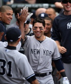 Jacoby Ellsbury of the New York Yankees is greeted by teammates in the dugout after hitting a solo home run in the 10th inning against the Chicago...