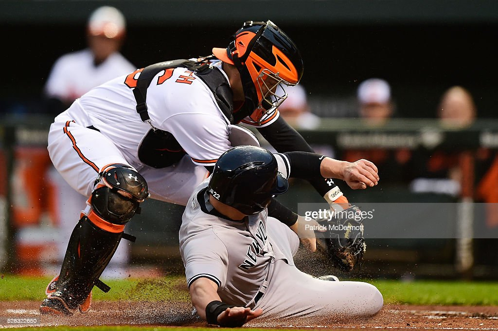Jacoby Ellsbury of the New York Yankees is tagged out at home plate by Caleb Joseph of the Baltimore Orioles in the first inning during a baseball...