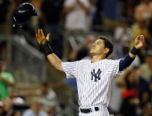 Jacoby Ellsbury of the New York Yankees reacts by throwing his helmet in the air after finding out the the run he scored on a stolen base and a two...