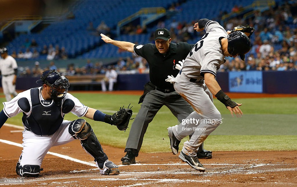 Jacoby Ellsbury #22 of the New York Yankees scores in front of catcher Bobby Wilson #46 of the Tampa Bay Rays off of a single by Mark Teixeira #25 as home plate umpire Dan Iassogna #58 makes the call during the first inning of a game on May 13, 2015 at Tropicana Field in St. Petersburg, Florida.