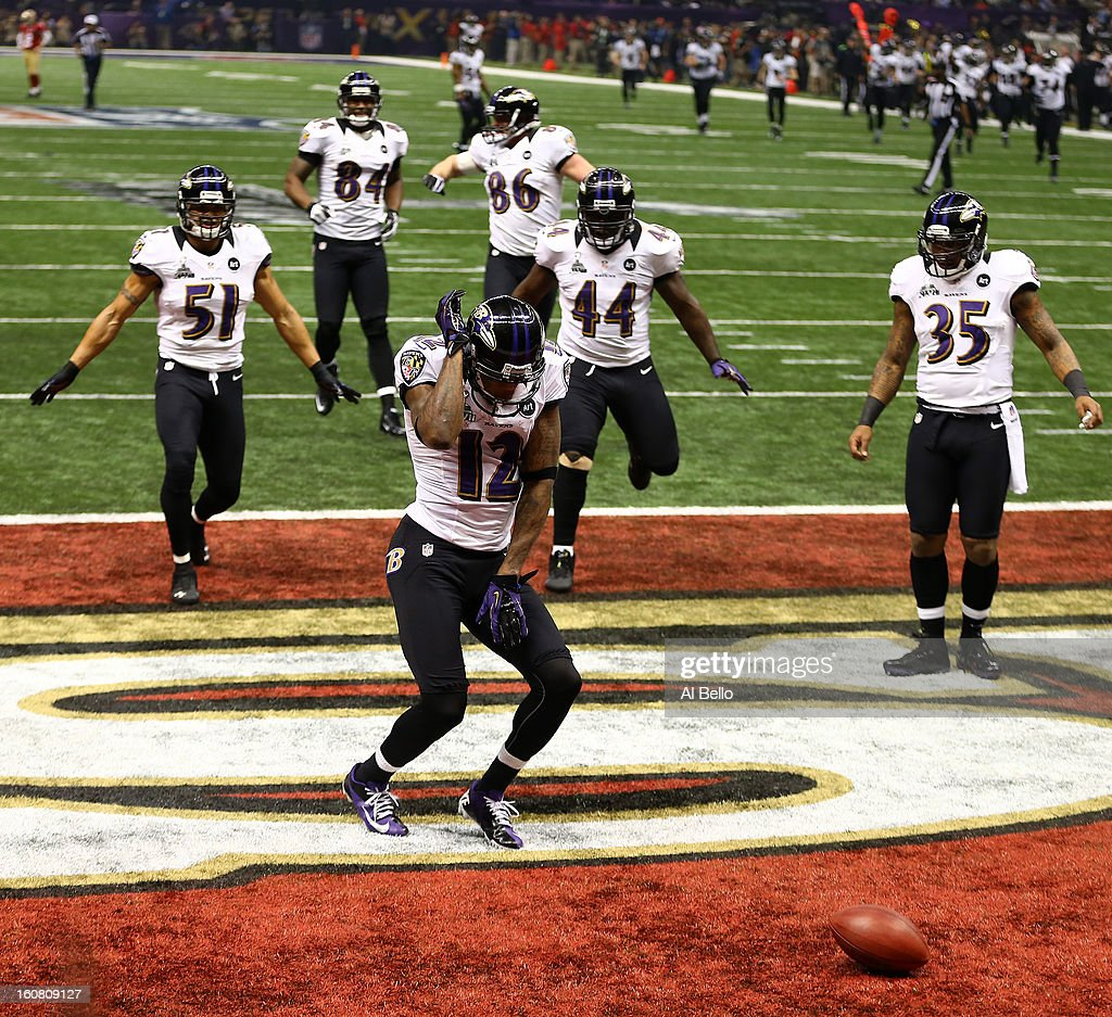 Jacoby Jones #12 of the Baltimore Ravens celebrates with teammates after he returned a kick-off 108-yards for a touchdown to open up the second half against Tramaine Brock #26 of the San Francisco 49ers during Super Bowl XLVII at the Mercedes-Benz Superdome on February 3, 2013 in New Orleans, Louisiana. The Ravens won 34-31.