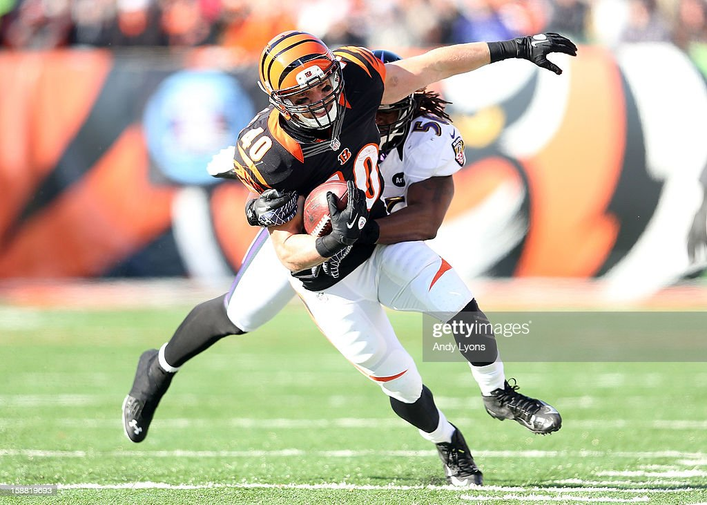 Jacoby Jones #12 of the Baltimore Ravens is tackled by Adam Jones #24 of the Cincinnati Bengals during the NFL game at Paul Brown Stadium on December 30, 2012 in Cincinnati, Ohio.