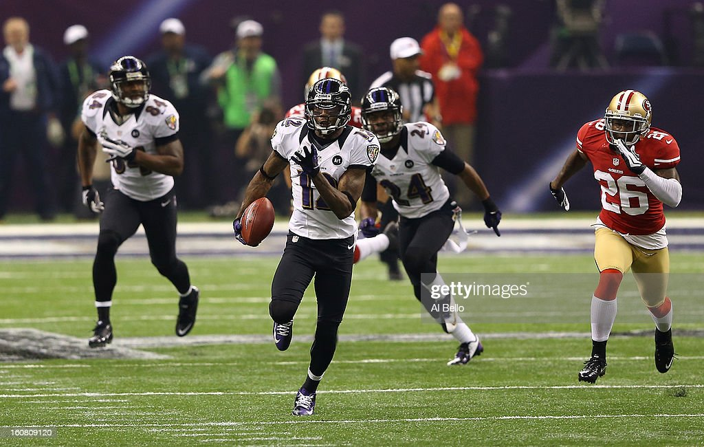 Jacoby Jones #12 of the Baltimore Ravens returns a kick-off 108-yards for a touchdown to open up the second half against Tramaine Brock #26 of the San Francisco 49ers during Super Bowl XLVII at the Mercedes-Benz Superdome on February 3, 2013 in New Orleans, Louisiana. The Ravens won 34-31.