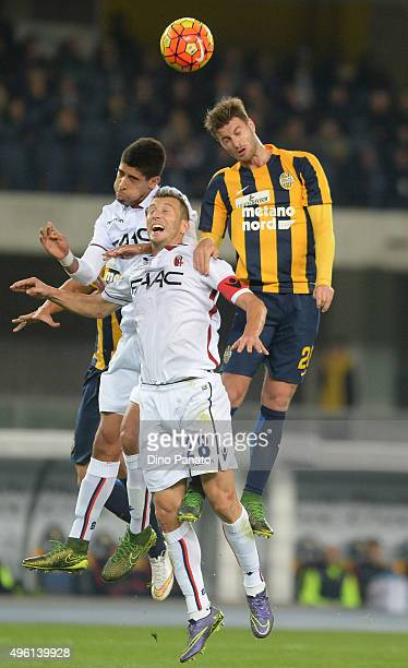 Jacopo Sala of Hellas Verona battles for an aerial ball with Daniele Gastaldello of Bologna FC during the Serie A match between Hellas Verona FC and...